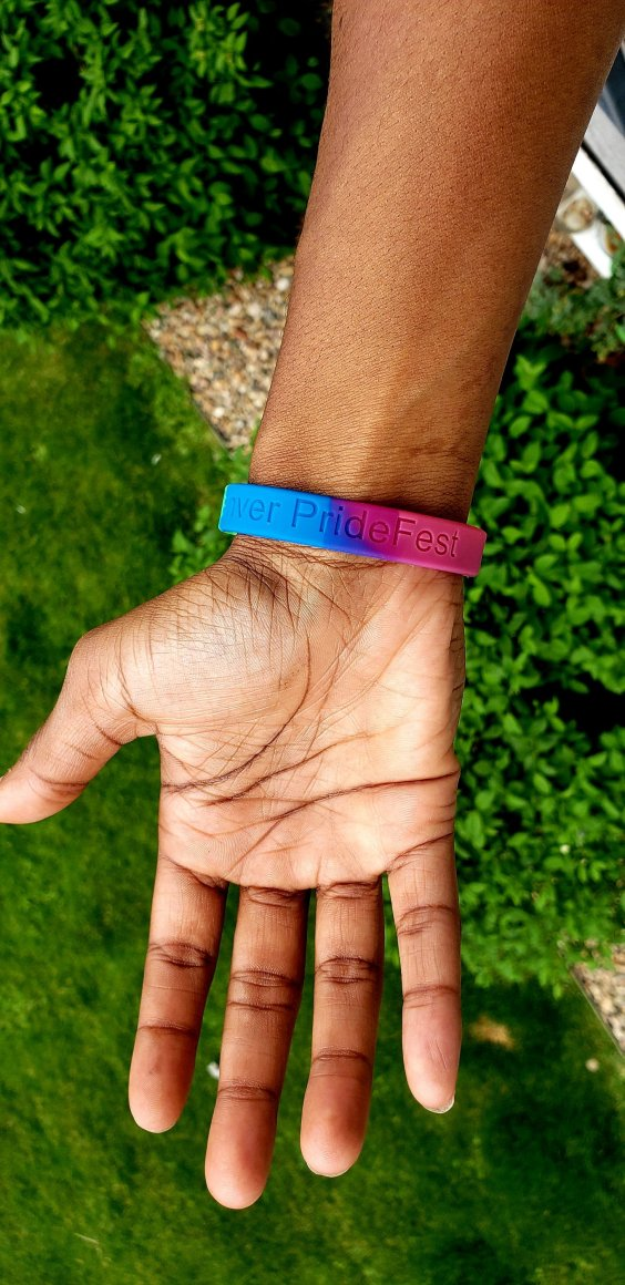 Photo of a person's arm and hand wearing a rainbow LGBTQ+ Pride bracelet