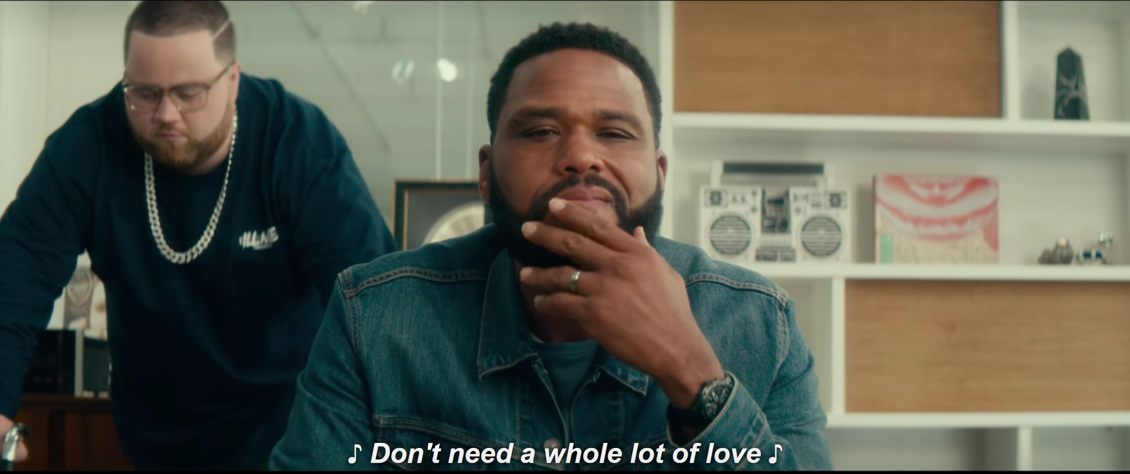 image of Romelo (Anthony Anderson) sitting stroking beard while Terrence (Paul Walter Hauser) stands behind him