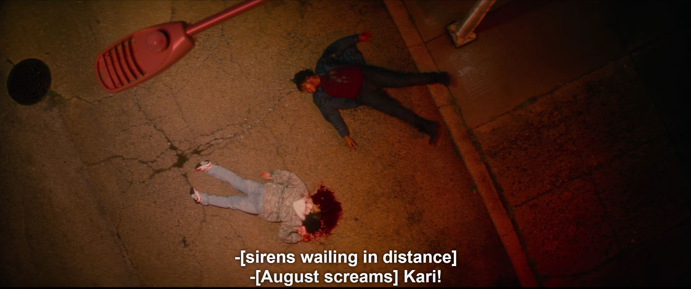 aerial view of August and Kari lying in street after shooting