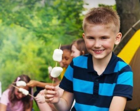 child enjoying marshmallows outdoors