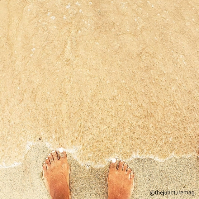 photography of feet in sand and water at beach on sunny day