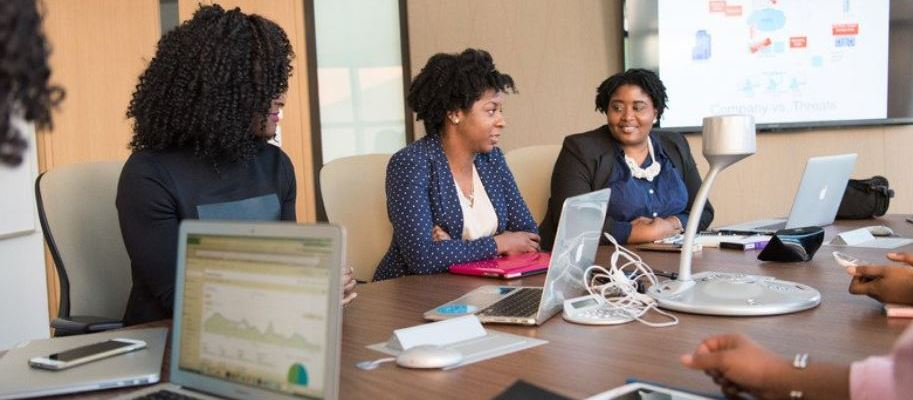 image of black women sitting in work conference room