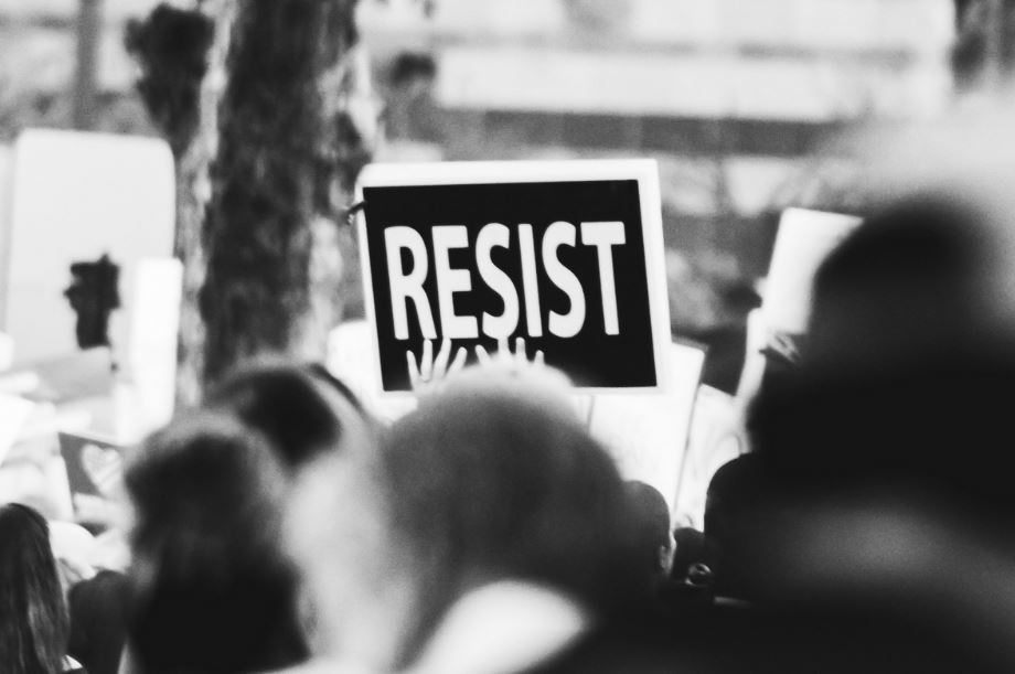 person holding up sign that says, 'resist'