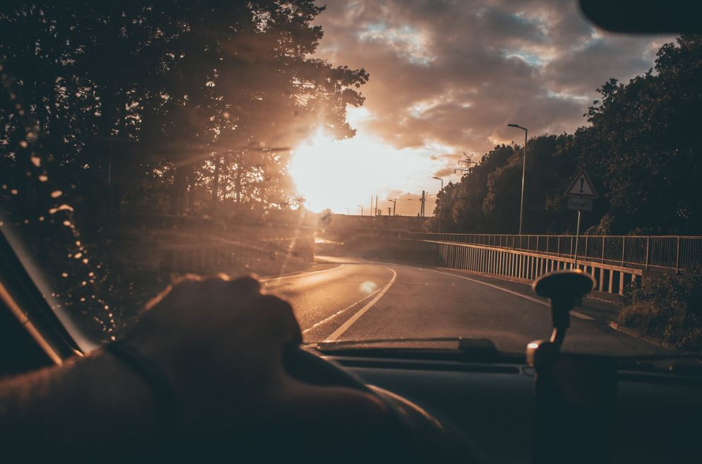 image of person driving down road with sun in the distance