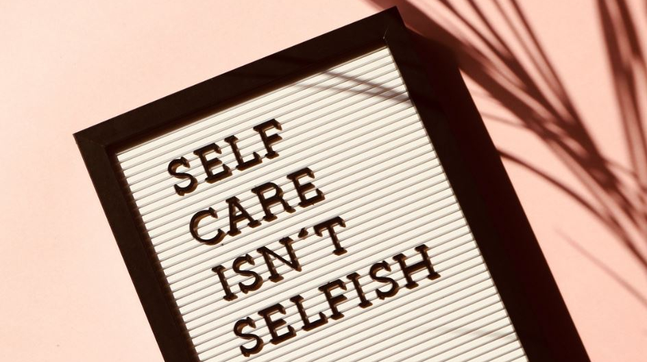 image of a board against a pink background with the quote 'self care isn't selfish' on the board. A shadow of a plant is in the image